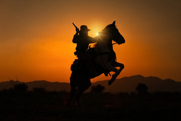 Silhouette Cowboy holding short gun and riding a horse