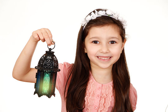 Happy young Muslim girl playing with lantern in Ramadan
