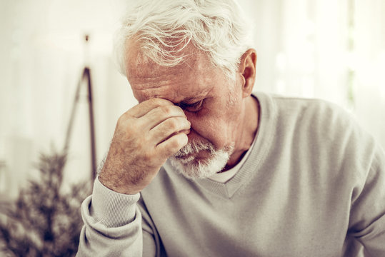 Old sick grey-haired man in beige sweater feeling terrible pain