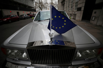 A Rolls Royce car with an EU flag attached to it is seen on a street in London