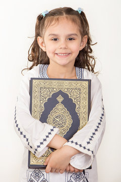 Happy young Muslim girl holding Holy Quran and wearing Islamic costume in Ramadan