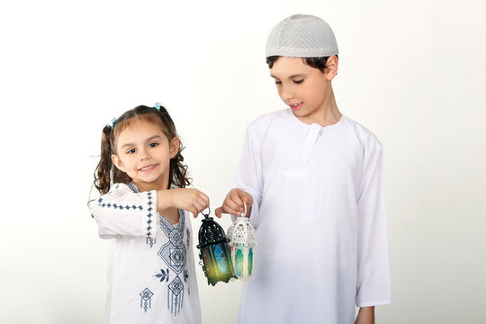 Happy Family in Ramadan - Cute brother and sister playing with Ramadan lanterns - celebrating the holy month of Ramadan