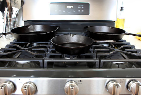 Modern stainless steel gas stove with cast iron skillets in a home kitchen.