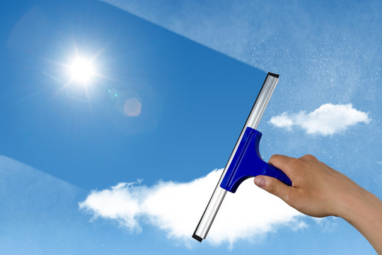 squeegee cleaning a dirty window, spring cleaning concept, blue sky with copy space