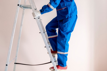 worker craftsman step up the ladder to repair home  f