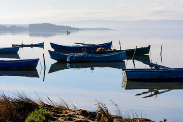 Old fishing boats with bright colors at dawn on the lake.