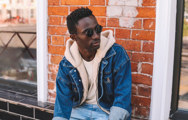 Wall Mural - Fashion portrait african man wearing jeans jacket sitting on city street over brick textured wall background