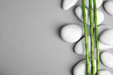 Zen stones and bamboo on grey background, top view with space for text