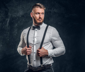 Stylishly dressed young man in shirt with bow tie and suspenders. Studio photo against a dark wall background