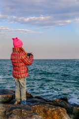 A girl in a pink jacket and a pink hat takes pictures on a mobile phone outdoors