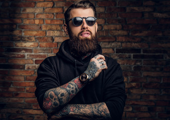 A stylish tattooed guy in a black hoodie and sunglasses. Studio photo against a brick wall