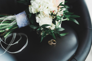 Beautiful toned picture with wedding rings against the background of a bouquet of flowers