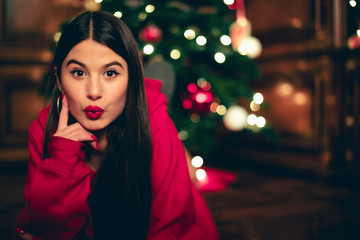 Portrait of teenage girl with Christmas tree in the background pouting mouth