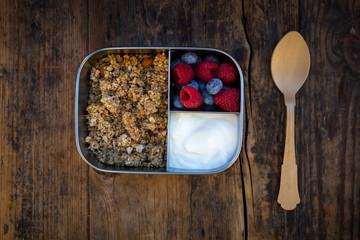 Breakfast box with granola, quinoa nuts, greek yogurt, blueberries and raspberries