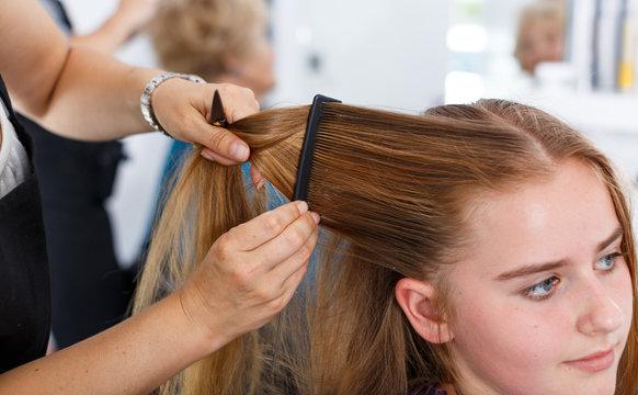 Closeup of teen girl getting haircutting
