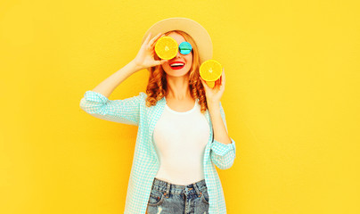 Summer portrait happy smiling woman holding in her hands slices of orange hiding her eyes in straw hat on colorful yellow background