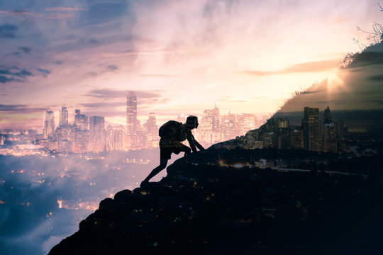 silhouette of man climbing up mountain overlooking city