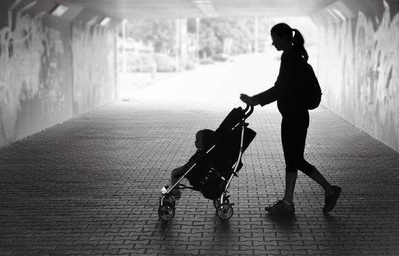 Single mother walking in city tunnel baby in stroller. People dark sad setting.