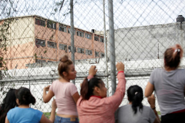 Relatives of inmates listen to inmates calling out from their cells as some other inmates were transferred to another prison, at the Topo Chico penitientiary in Monterrey