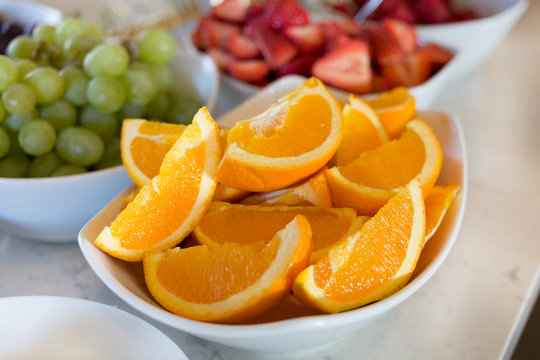 Sliced Oranges and fresh strawberries and green grapes