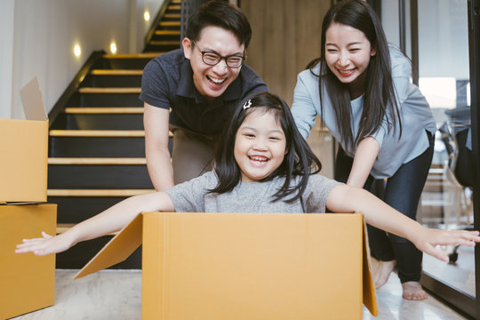 Portrait of happy Asian family moving to new house with cardboard boxes.