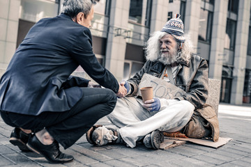 Pleasant smiling rich man shaking hand of poor grey-haired homeless Fotomurales