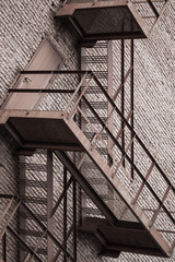 Metal stairway over red brick wall
