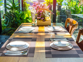 Dining table set in restaurant with romantic sunshine