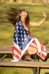 woman celebrating on independence day 4th of july with flag of american in the park at sunset