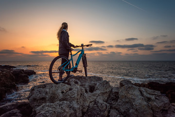 Woman with a bike in the nature / Rear view of a woman with a bike enjoys the view of sunrise at the rocky Black Sea coast