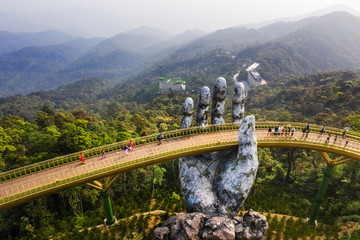 Top aerial view of the famous Golden Bridge is lifted by two giant hands in the tourist resort on Ba Na Hill in Danang, Vietnam. Wall mural