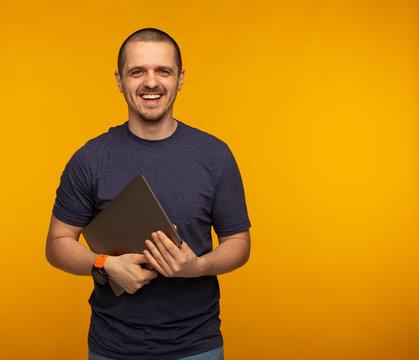 Freelancer or developer laughting and holding laptop