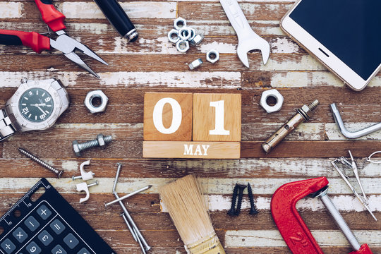 1st May. Happy International Worker's day or Labour Day background concpet.  wooden block calendar 1 May and handy tools and office men's accessories on grunge wooden table texture background.
