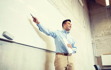 education, school, business, teaching and people concept - happy teacher or businessman pointing marker to white board at lecture