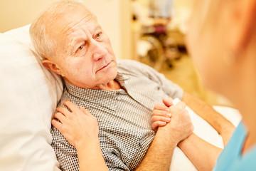Pflegedienst tröstet kranken Senior Mann