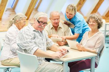 Pflegekraft hilft Senioren im Computerkurs