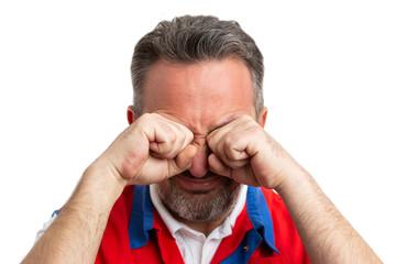 Closeup of supermarket employee rubbing eyes.
