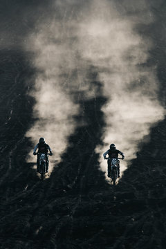 Two friends racing on custom retro style cafe racer black motorcycles on the black lava sand at sunrise on mount Batur, Bali, Indonesia