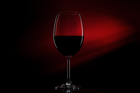 Silhouette of glass of red wine on black to red gradient background. Close-up studio shot.