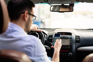 Man driver using smart phone in car modern