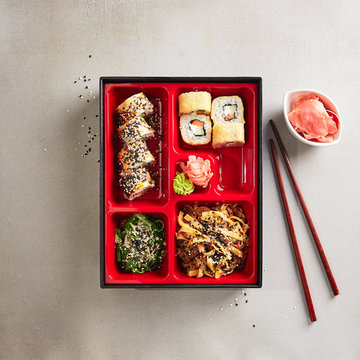 Japanese Bento Box with Sushi Rolls, Salad and Main Course Top View