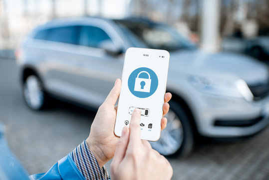 Locking car using mobile application on a smart phone. Concept of remote control and car protection through the internet