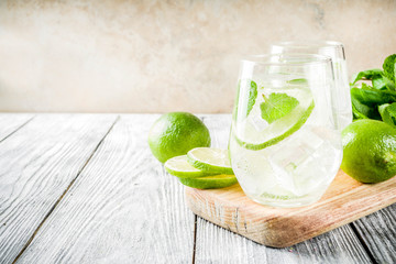 Summer sour drink, with lime and mint, homemade cocktail mojito in two glasses, white wooden background, with fresh limes, mint leaves, ice cubes, copy space