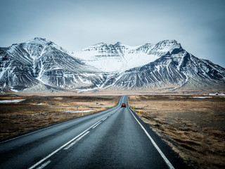 Modern car riding on asphalt countryside road towards magnificent snowy mountains during trip through Iceland