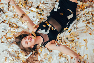 Party over. Free alone. Beauty lying on bed scattered with confetti. Happy, smiling woman. Memories and relaxation.