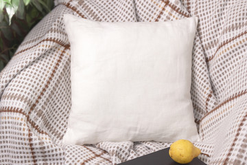 White linen pillow on a chair in cozy room, mockup
