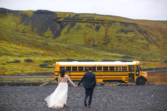 Beautiful wedding couple posing with yellow school bus