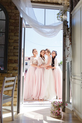 bride with three girlfriends of the bride hugging at the loggia in the morning at the wedding