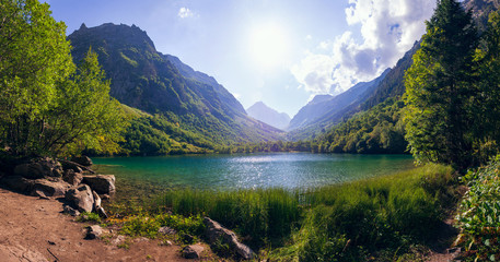 A huge panorama of the High-mountainous Baduk lake among the high Caucasian mountains and beautiful trees. Sunny summer day. Wall mural