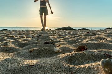 Frau läuft am Strand im Sand bei Sonnenuntergang